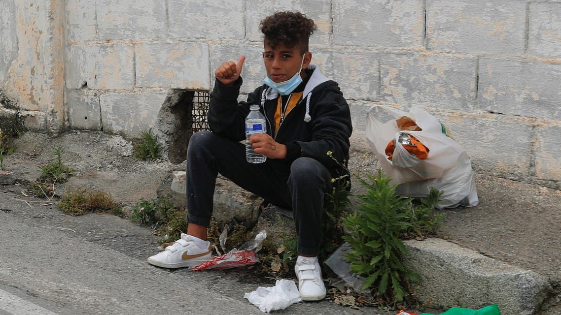 A migrant minor sits by the road after refusing to enter a facility prepared for migrants, near the Spanish-Moroccan border, after thousands of migrants swam across this border during the last days, in Ceuta, Spain, May 21, 2021. REUTERS/Jon Nazca