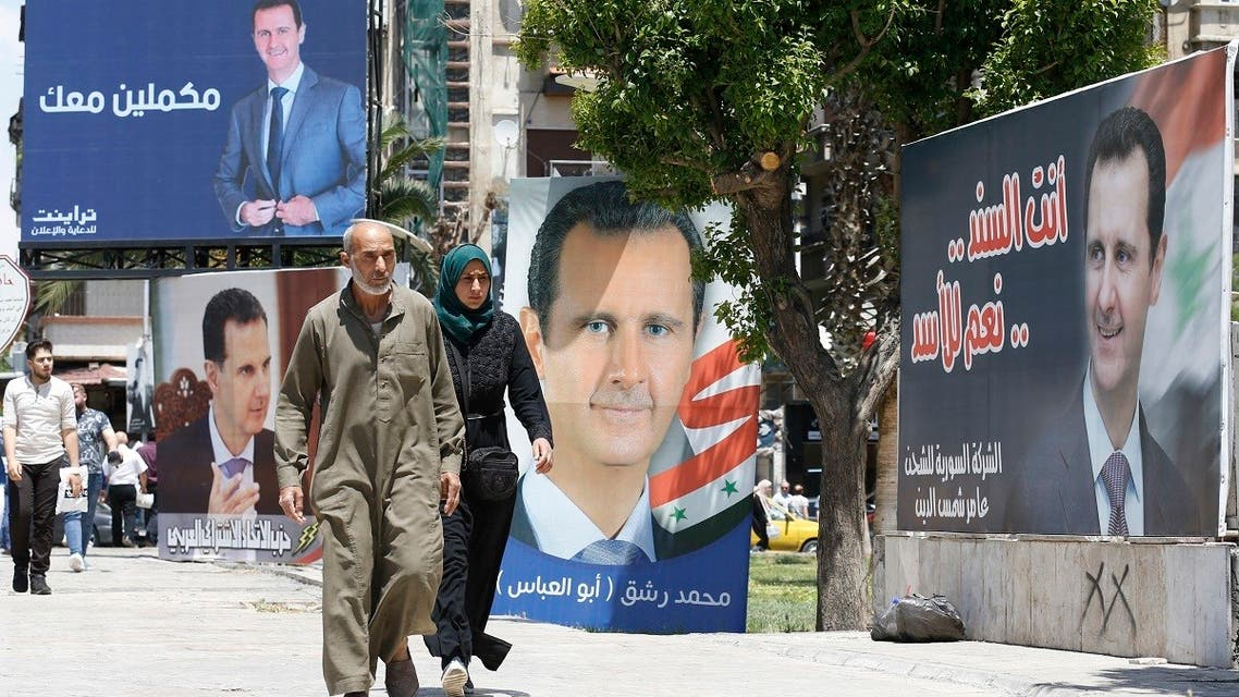 In this file photo taken on May 24, 2021, People walk next to election campaign billboards depicting Syrian President Bashar al-Assad, a candidate for the upcoming presidential vote, in the capital Damascus. (Louai Beshara/AFP)