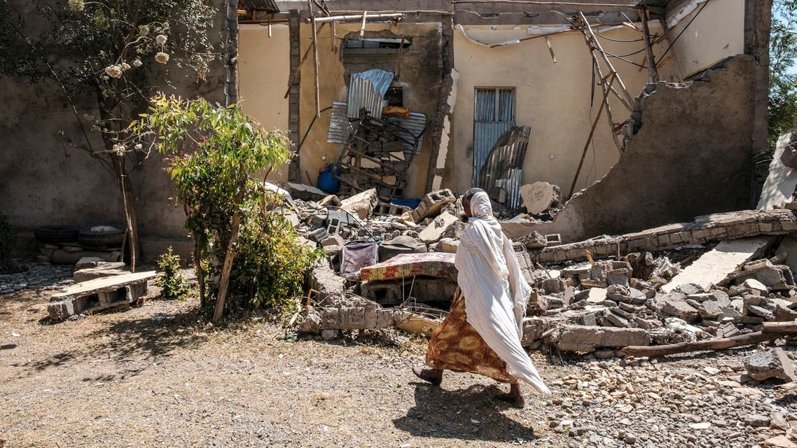 (FILES) In this file photograph taken on March 1, 2021, a woman walks in front of a damaged house in Wukro, north of Mekele which was shelled as federal-aligned forces entered the city. Eritrean soldiers are blocking and looting food aid in Ethiopia's war-hit Tigray region, according to government documents obtained on April 27, 2021, by AFP, stoking fears of starvation deaths as fighting nears the six-month mark.
