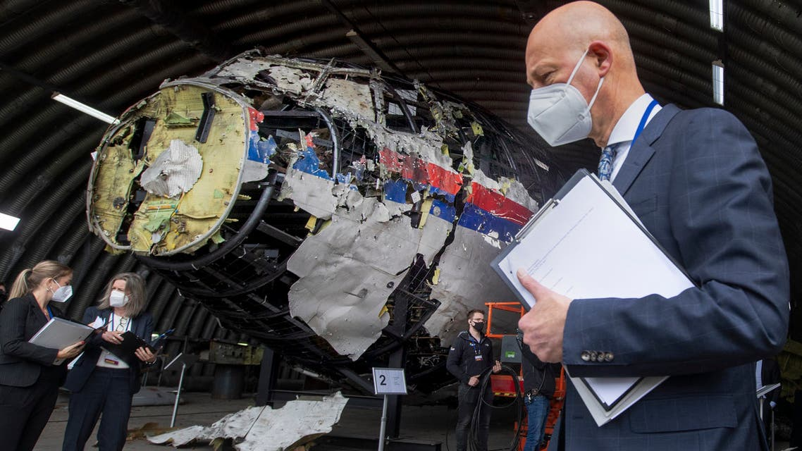 Presiding judge Hendrik Steenhuis (R) points as he and other trial judges and lawyers stand next to the reconstructed wreckage of Malaysia Airlines Flight MH17, at the Gilze-Rijen military airbase, southern Netherlands, on May 26, 2021. Judges inspect wreckage of flight MH17 as part of criminal trial of four suspects. (File photo: AFP)