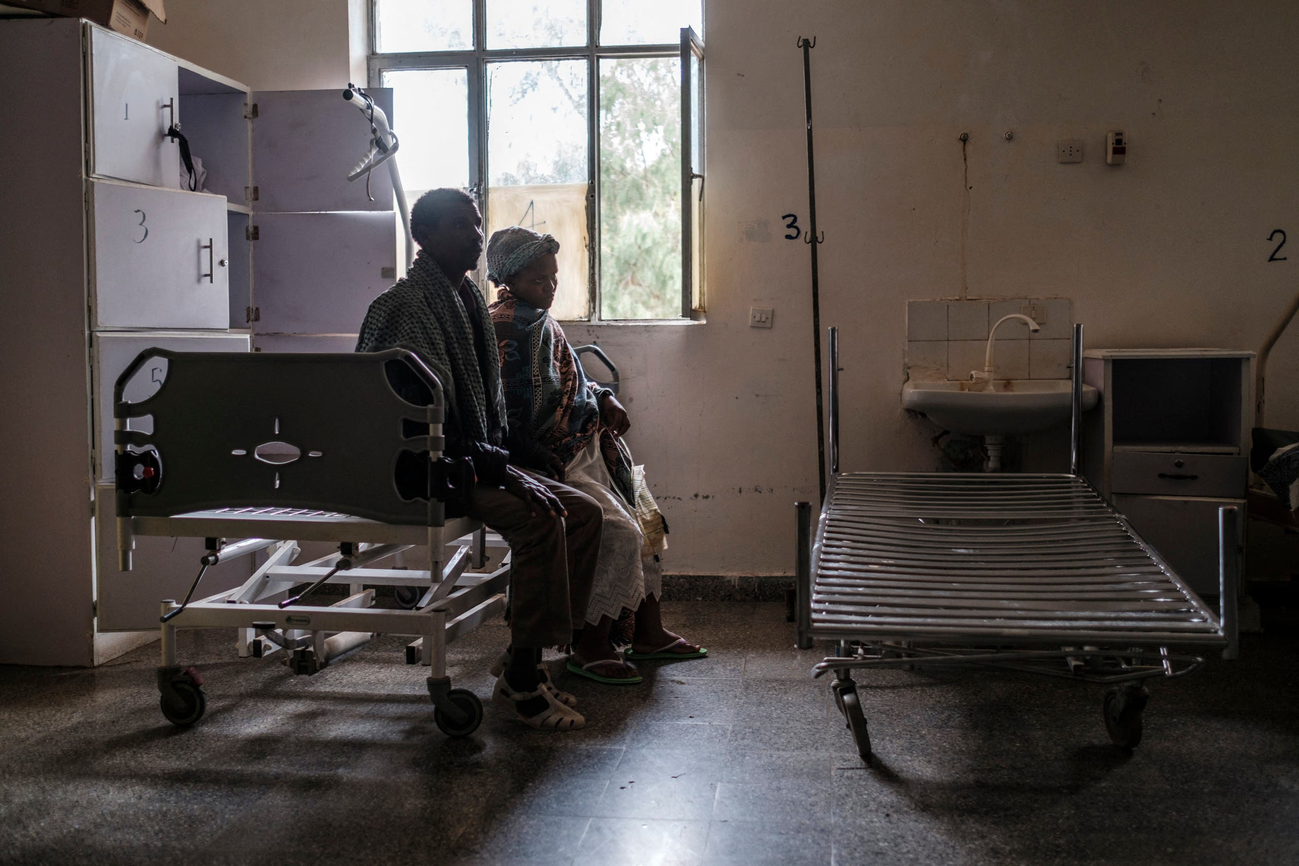 شخصان يحلسان داخل مستشفى في تيغراي تم نهب ممتلكاته