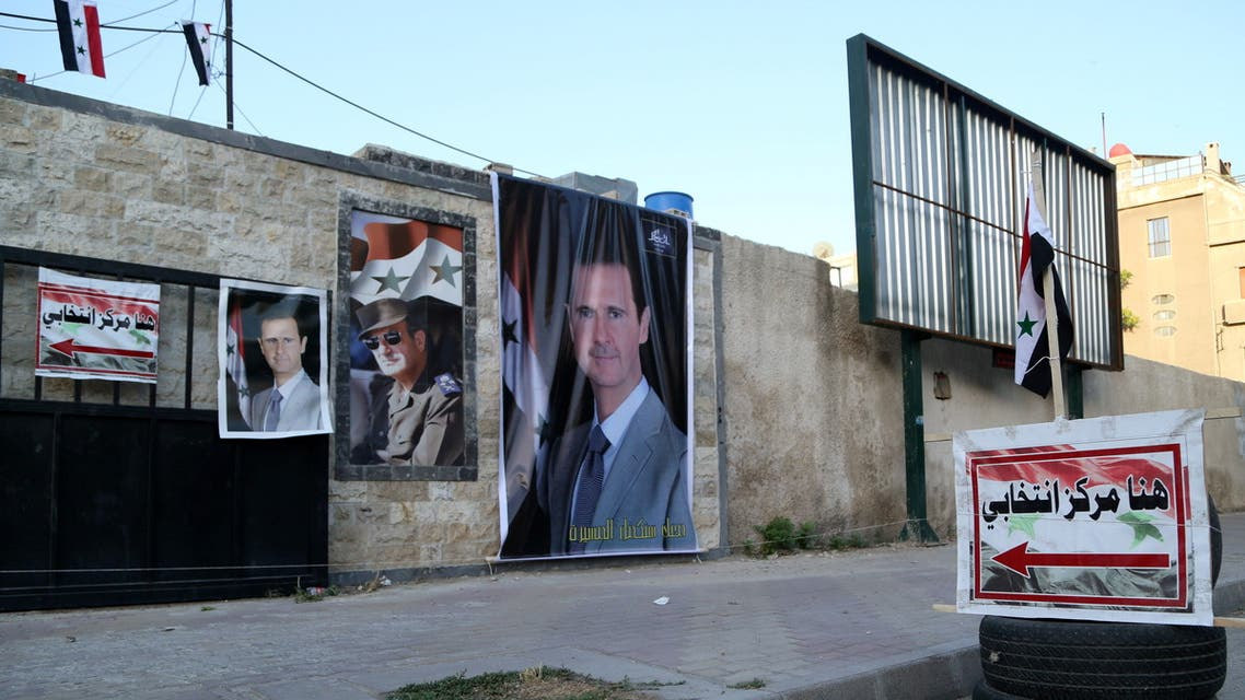 Posters of Syria's President Bashar al-Assad are seen outside a polling station before polls open for the presidential elections, in Damascus, Syria May 26, 2021. (Reuters)
