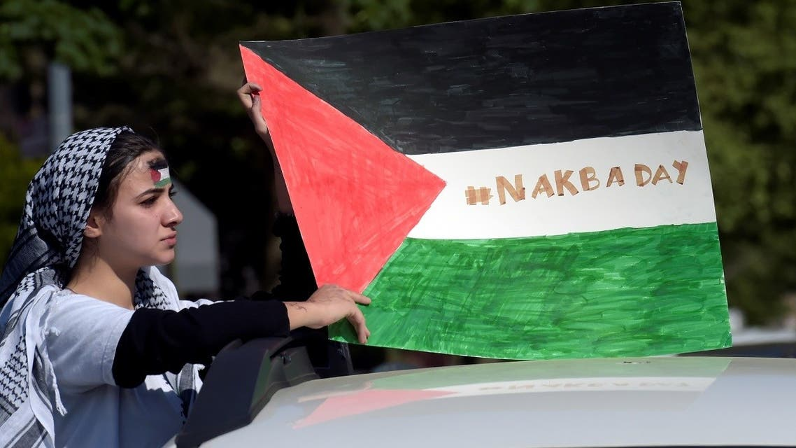 A pro-Palestinian supporter holds a Palestine flag during a protest against Israeli attacks on Gaza amid days of conflict between the two sides, in Brooklyn. (Reuters)