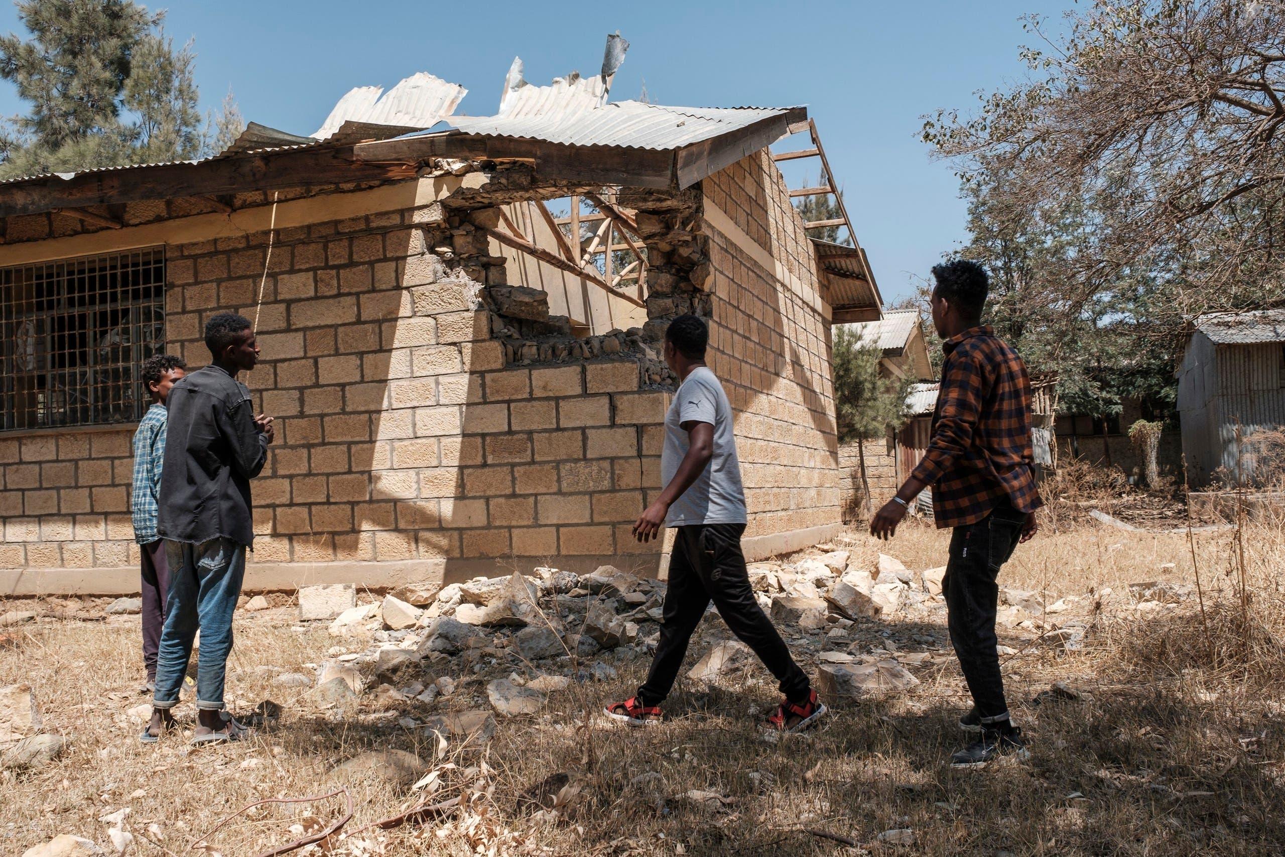 شباب يعاينون الدمار الذي لحق بالمباني في تيغراي بسبب القتال