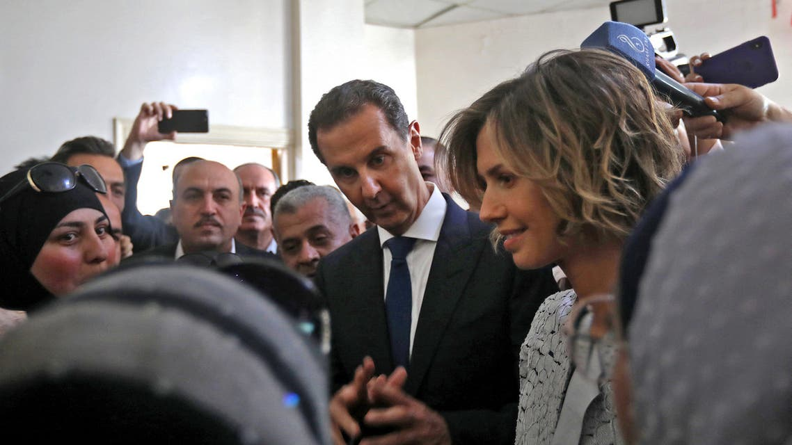 Syrian President Bashar al-Assad (C) and his wife Asma (R) talk to the crowd after casting their votes at a polling station in Douma, near Damascus on May 26, 2021, as voting began across Syria for an election guaranteed to return Assad for a fourth term in office. (AFP)