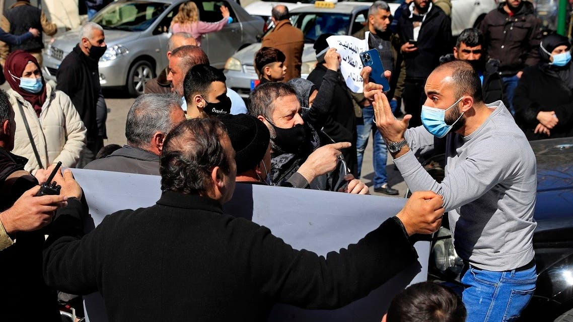 A man stuck in traffic argues with parents of Lebanese students who study abroad to reopen a road blocked during a protest demanding that banks allow the transfer of universities fees for their children, in Beirut, Feb. 22, 2021. (AP)