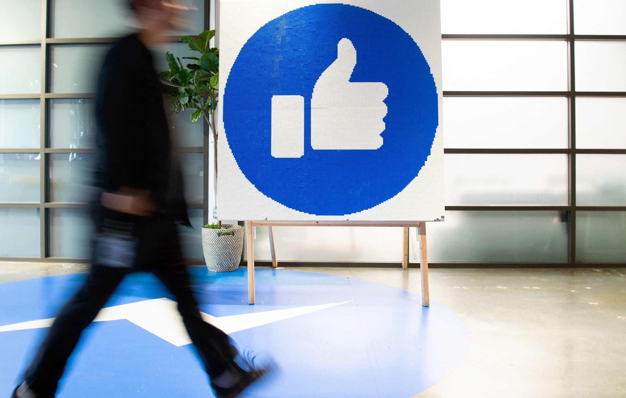 موظف في فيسبوك يمر أمام علامة إعجاب كبيرة في مقر الشركة في كاليفورنيا