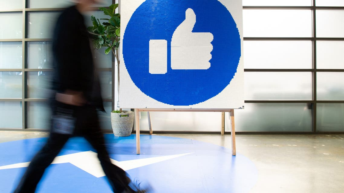 A Facebook employee walks by a sign displaying the like sign at Facebook's corporate headquarters in California. (File Photo: Reuters)