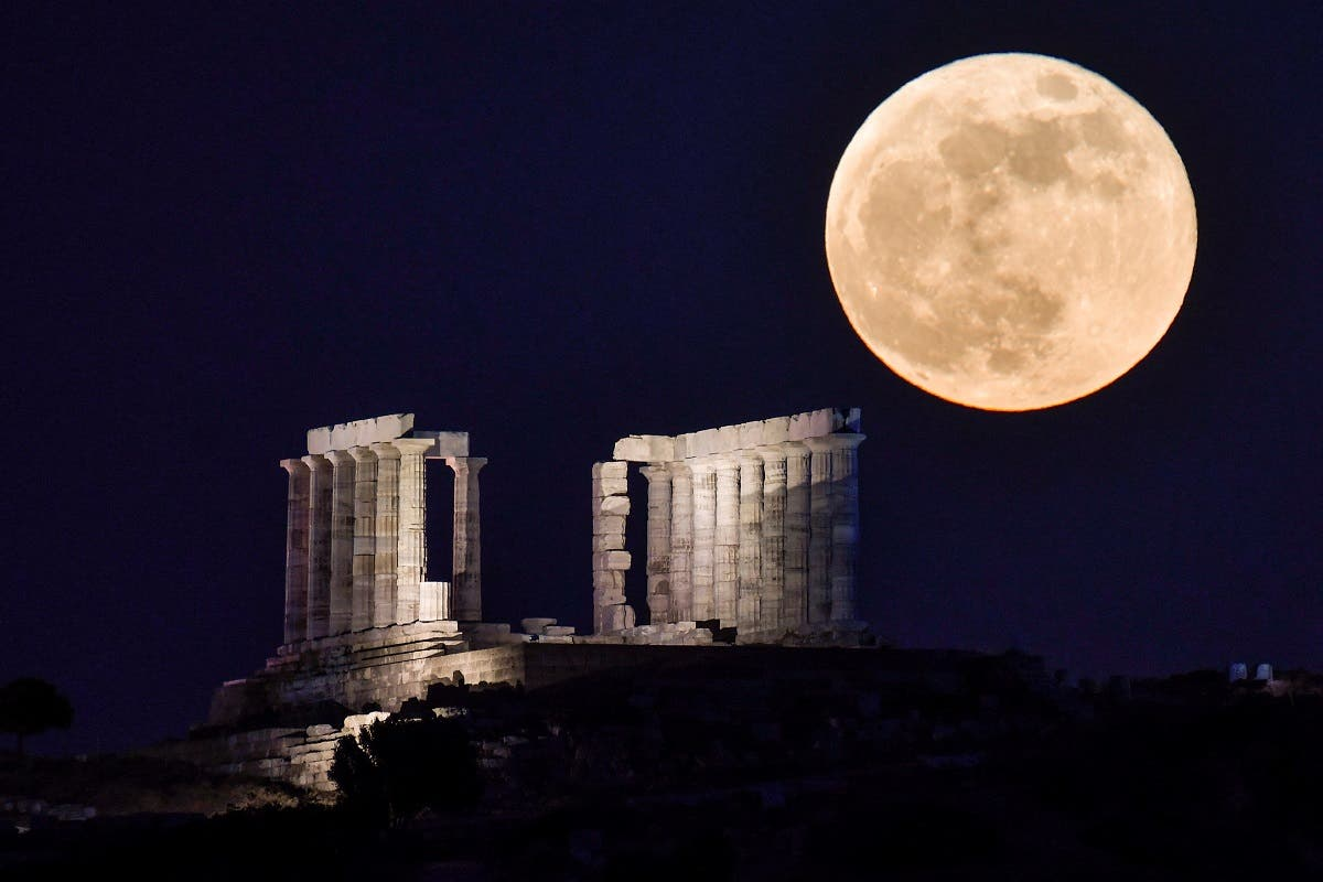 The flower full moon rises behind the Temple of Poseidon (neptun) at Cape Sounion, some 70 km south of Athens on May 26, 2021. (AFP)