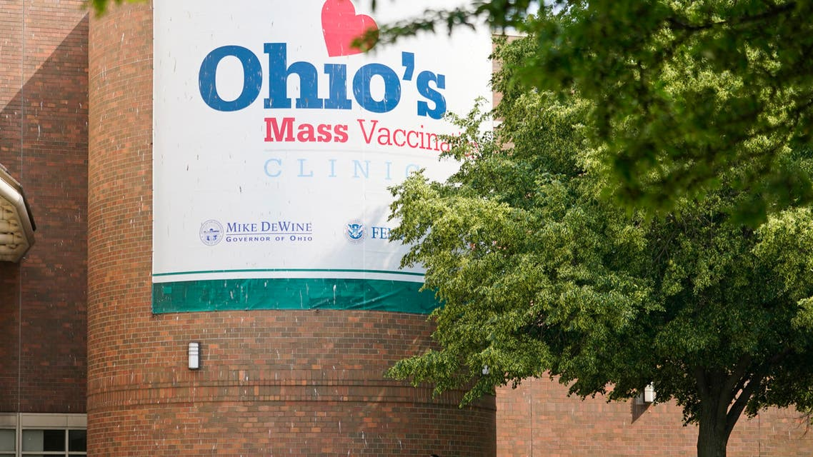 People walk past sign displayed for Ohio's COVID-19 mass vaccination clinic at Cleveland State University, Tuesday, May 25, 2021, in Cleveland. (AP)