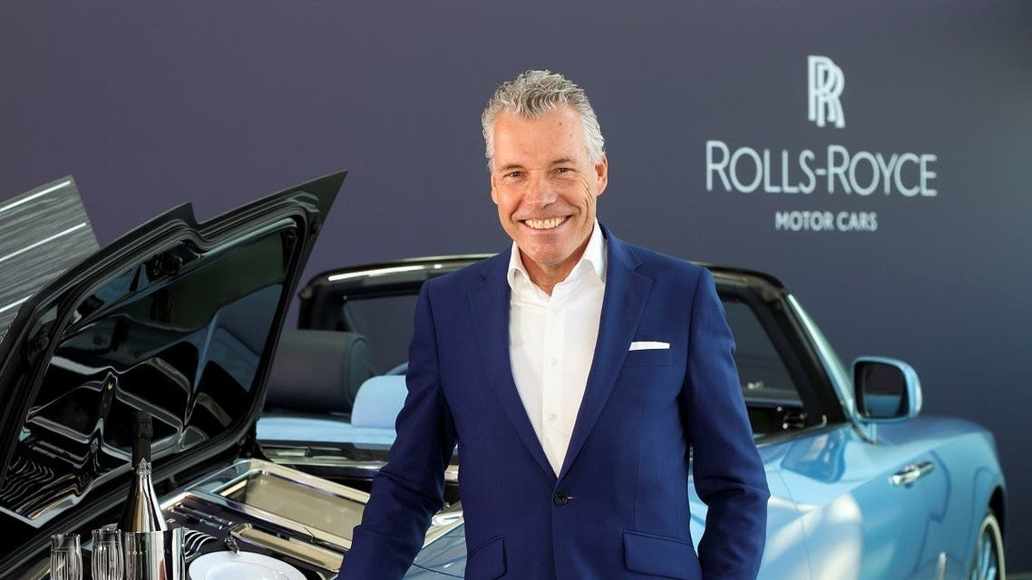 Torsten Muller-Otvos, CEO of Rolls-Royce, poses next to a handmade car described as 'the most refined picnic facility on earth,' at the company's factory in Goodwood, Britain May 27, 2021. (Reuters)