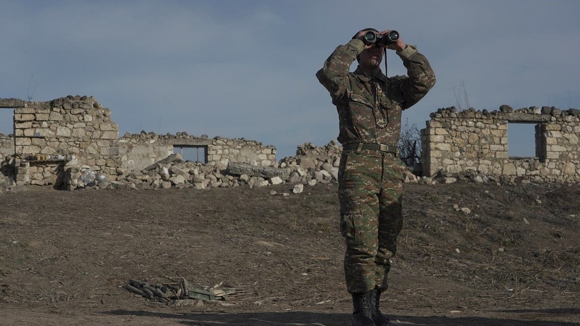 An ethnic Armenian soldier looks through binoculars as he stands at fighting positions near the village of Taghavard in the region of Nagorno-Karabakh, Jan. 11, 2021. (Reuters)