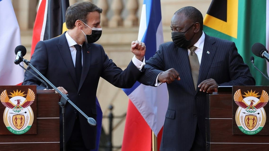 France's President Emmanuel Macron and South Africa's President Cyril Ramaphosa bump elbows after a news conference during a state visit, at the Union Buildings in Pretoria, South Africa, on May 28, 2021. (Reuters)