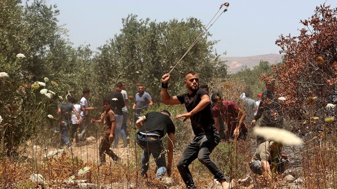 Palestinian protesters use slingshots to hurl stones at Israeli security forces amid clashes in the village of Baita, south of Nablus, in the occupied West Bank on May 28, 2021, following a demonstration against the establishment of Israeli outposts in their lands. (AFP)