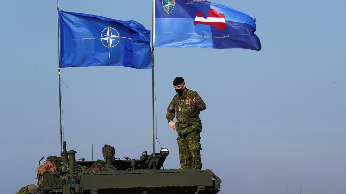 NATO and NATO's Enhanced Forward Presence battle group Latvia flags flutter during military exercise Crystal Arrow 2021 in Adazi, Latvia, on March 26, 2021 (Reuters)