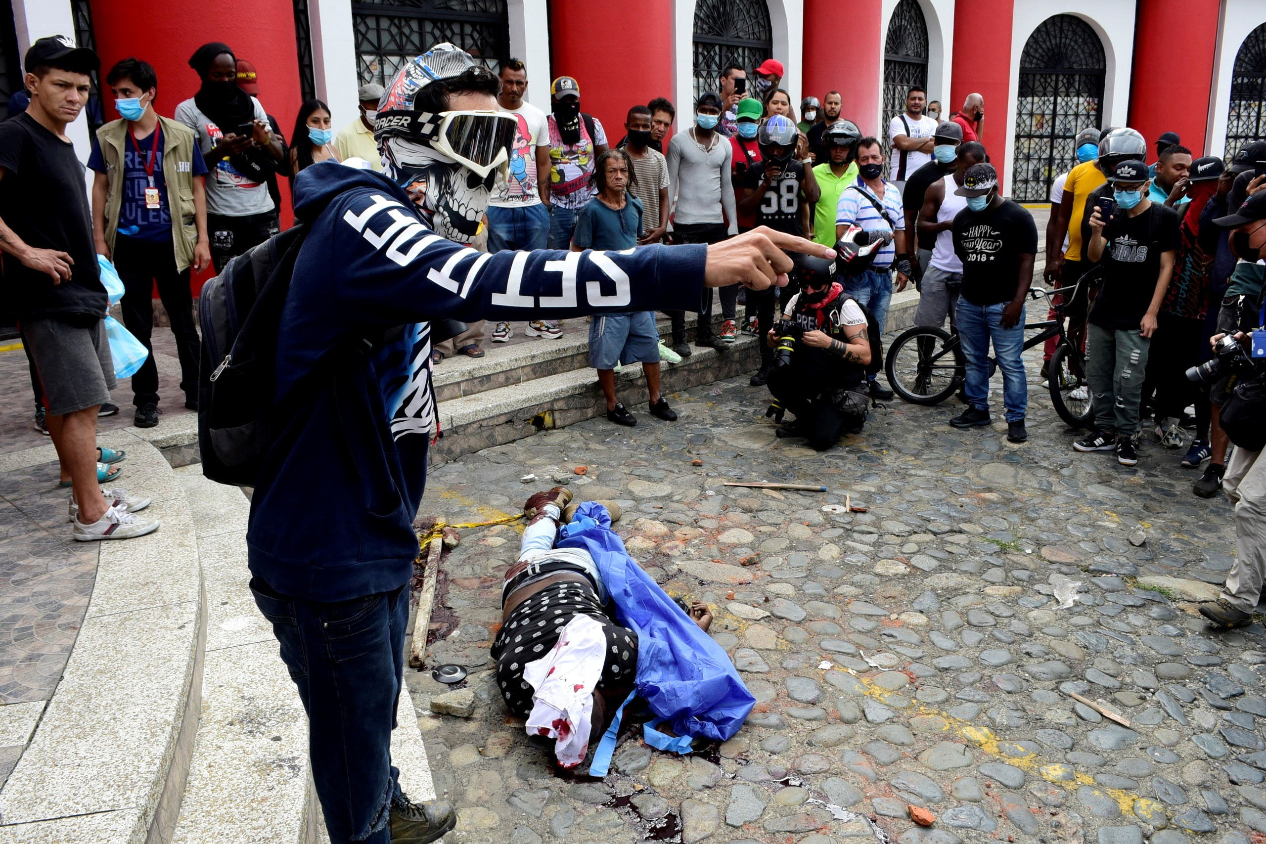 A demonstrator yells as he stands next to the body of an agent of the attorney general's investigative unit, who opened fire on civilians before being killed, as protests demanding government action to tackle poverty, police violence and inequalities in healthcare and education systems continue, in Cali, Colombia May 28, 2021. (Reuters)