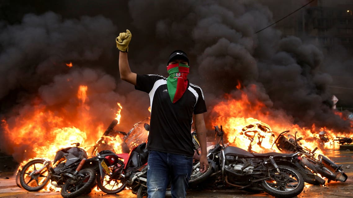 A demonstrator gestures as motorcycles that are are impounded for violating traffic regulations are seen on fire at the municipal yards, in Popayan, Colombia May 28, 2021. (Reuters)