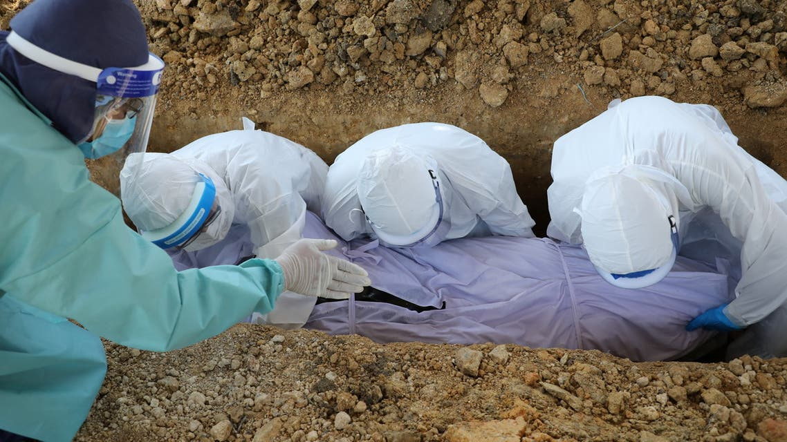 Malaysian Muslim cleric Rafie Zainal assists family members of a coronavirus disease (COVID-19) victim during a burial at a cemetery, in Gombak, Malaysia May 23, 2021.  (Reuters)