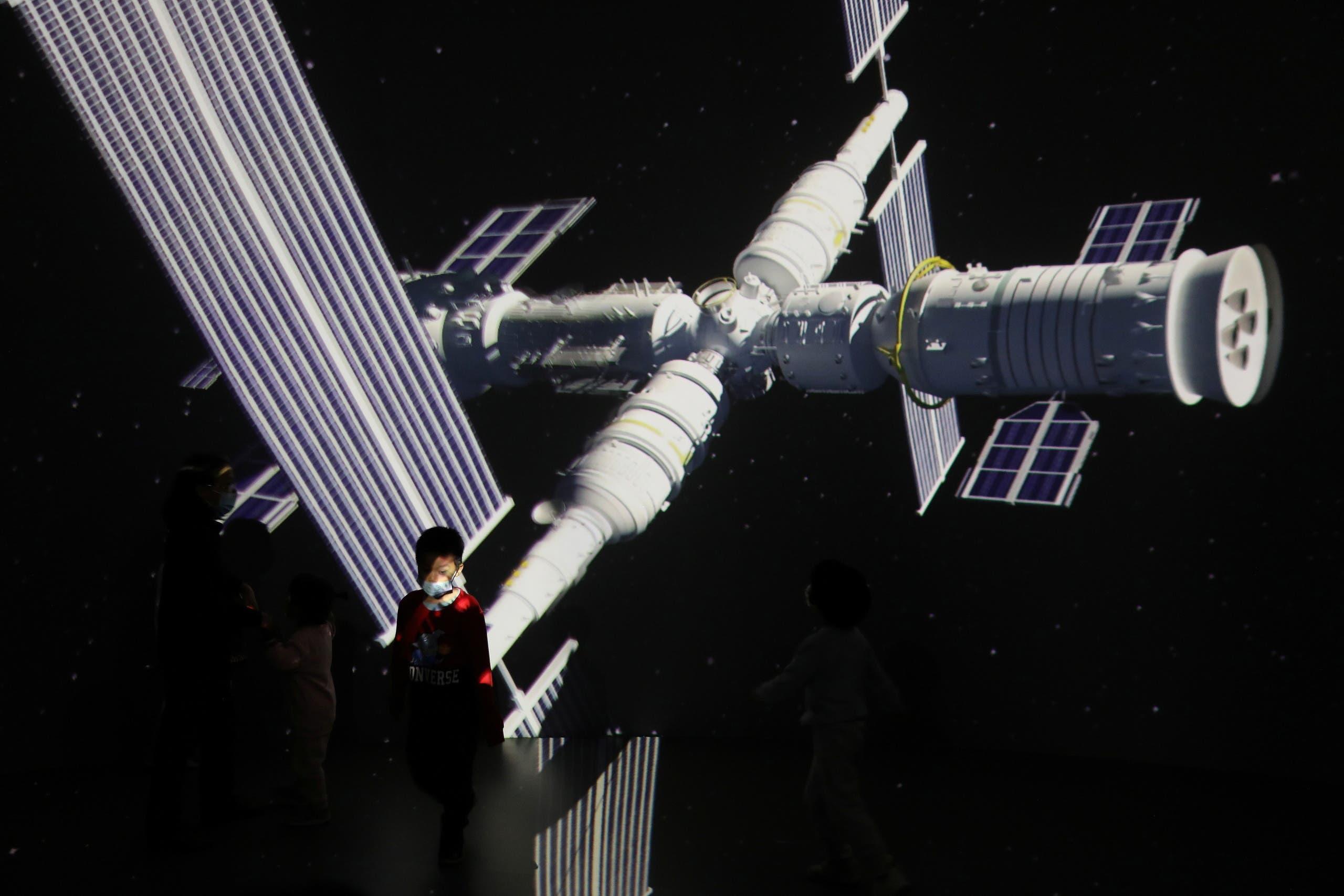 طفل يمشي في معرض في بكين امام صورة عملاقة لمحطة الفضاء الصينية