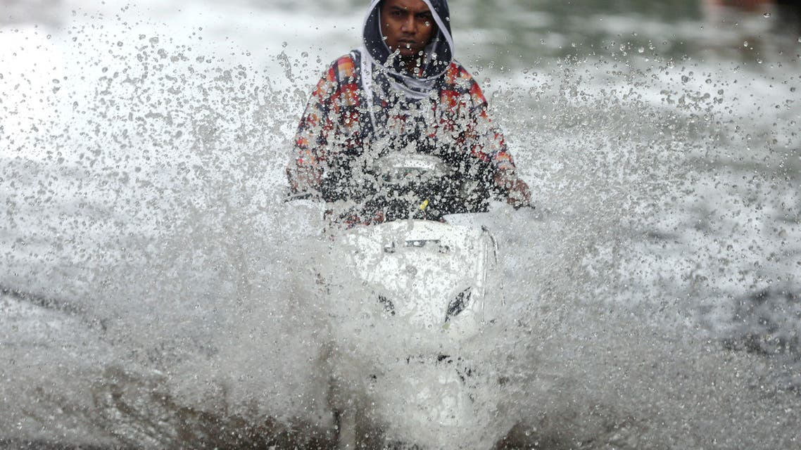 A person rides a scooter through a waterlogged road during monsoon rain showers in Mumbai, India, June 4, 2020. (Reuters)