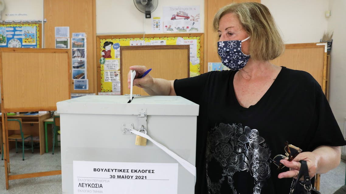 A woman wearing a protective face mask casts her vote during parliamentary elections at a polling station in Nicosia, Cyprus May 30, 2021. REUTERS/Yiannis Kourtoglou