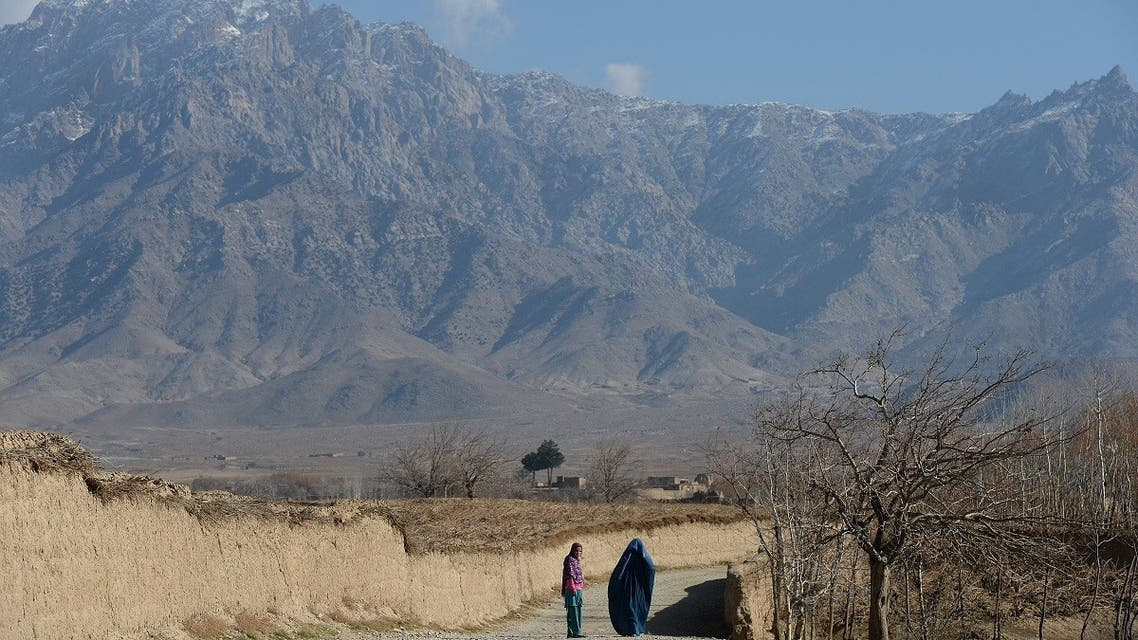 An Afghan girl watches as a burqa-clad woman walks at Darwazagi village, in Kapisa province on December 17, 2013. (File photo: AFP)