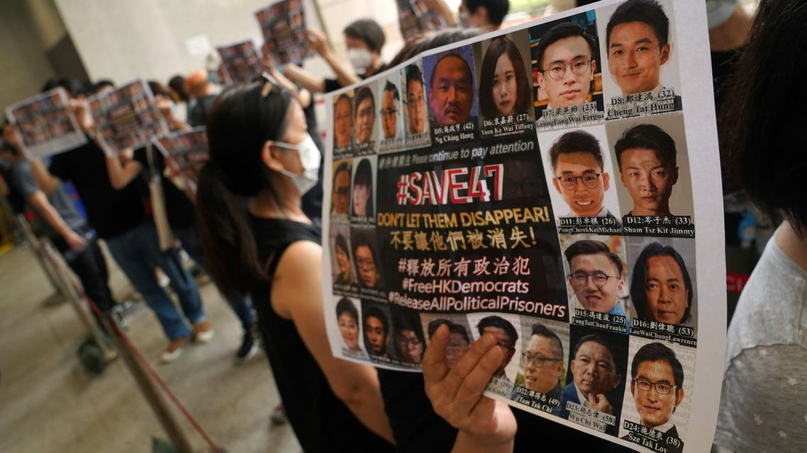 People hold signs to support pro-democracy activists charged with violating the national security law, as they queue up at West Kowloon Magistrates' Courts for a court hearing, in Hong Kong, China May 31, 2021. REUTERS/Lam Yik