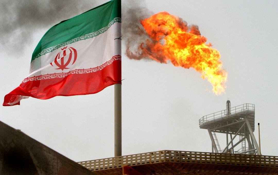 A gas flare on an oil production platform is seen alongside an Iranian flag. (Reuters)