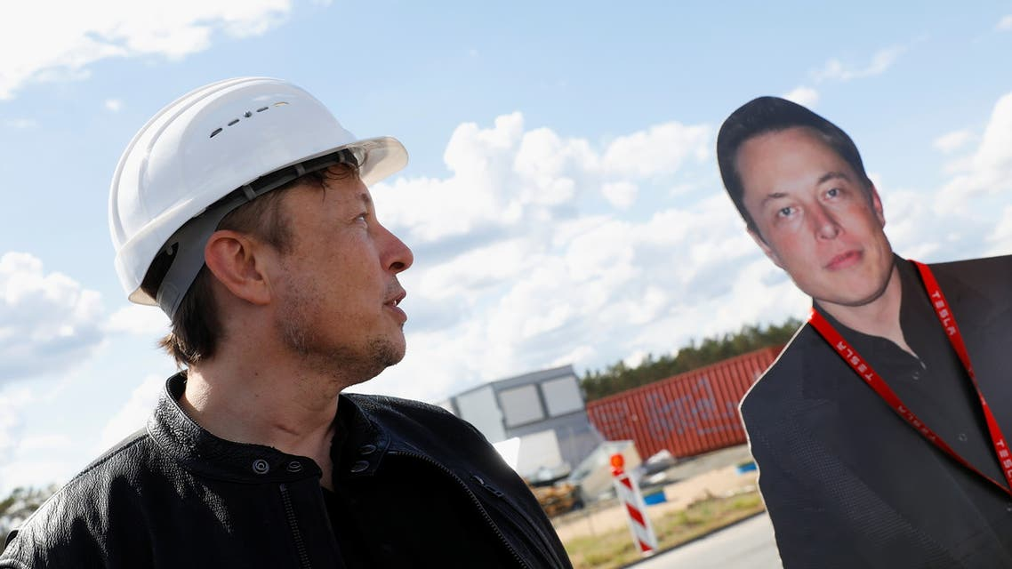 """إيلون ماسك ينظر إلى صورة له في موقع بناء مصنع """"تسلا"""" الجديد (رويترز)"""