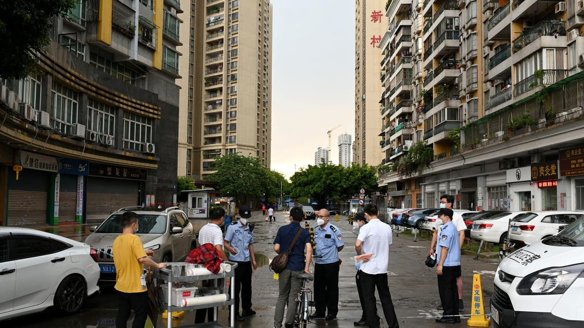 Police officers speak to people behind a police line near a residential area where only entering is allowed, following new cases of the coronavirus disease (COVID-19), in Guangzhou's Liwan district, Guangdong province, China May 29, 2021. (Reuters)