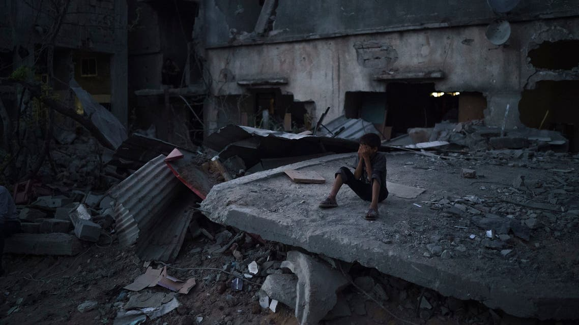A boy closes his eyes as he plays hide-and-seek at dusk in a neighborhood heavily damaged by airstrikes during an 11-day war between Gaza's Hamas rulers and Israel, Monday, May 31, 2021 in Beit Hanoun, Gaza Strip. (AP)