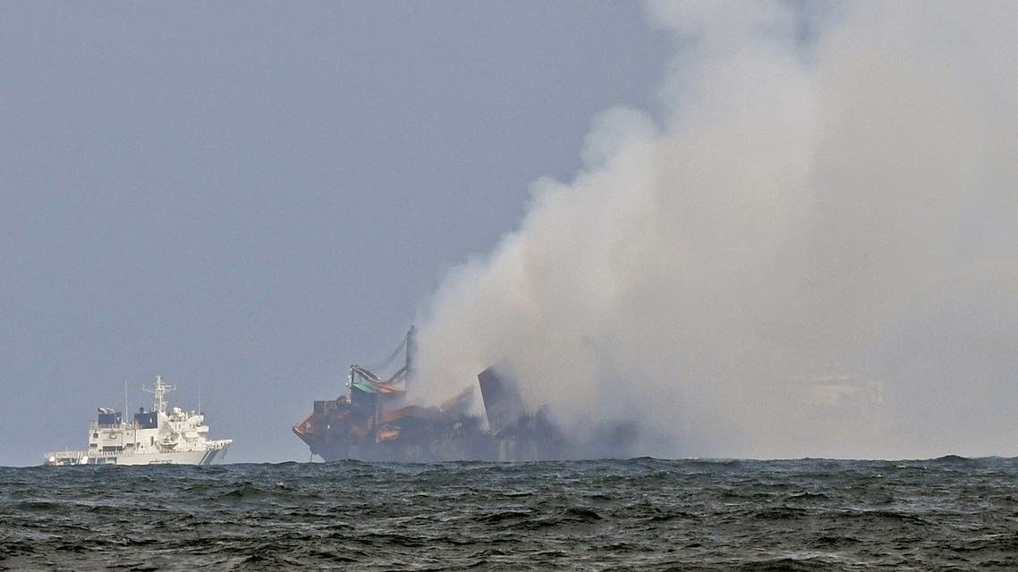 An Indian Coastguard ship (L) tries to douse off the fire as smoke billows from the Singapore-registered container ship MV X-Press Pearl, on a beach in Colombo on May 31, 2021. (Lakruwan Wanniarachchi/AFP)