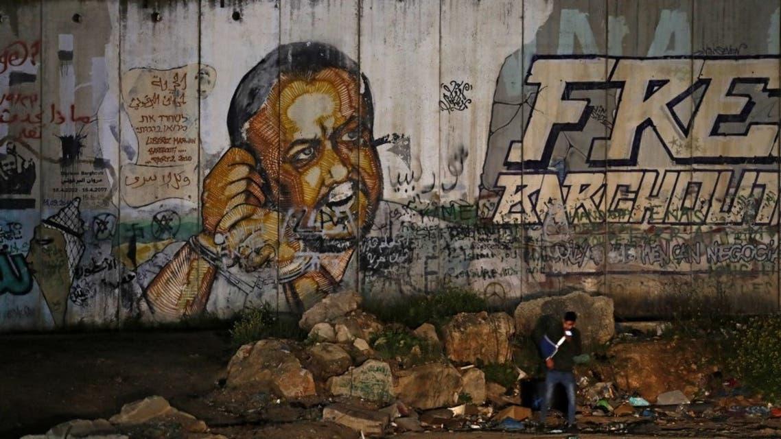 صورة تم التقاطها في 31 مارس 2021 بالقرب من حاجز قلنديا الإسرائيلي ، بين القدس ورام الله ، تظهر لوحة جدارية للأاسير الفلسطيني من حركة فتح مروان البرغوثي