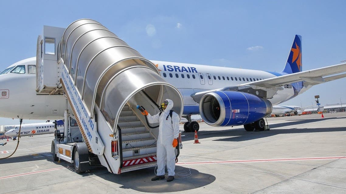 An Israeli worker in full hazmat suit sprays disinfectant on the boarding stairs of an Israir Airlines Airbus A320 airplane, at the Ben Gurion International Airport near the central Israeli city of Tel Aviv. (File photo: AFP)