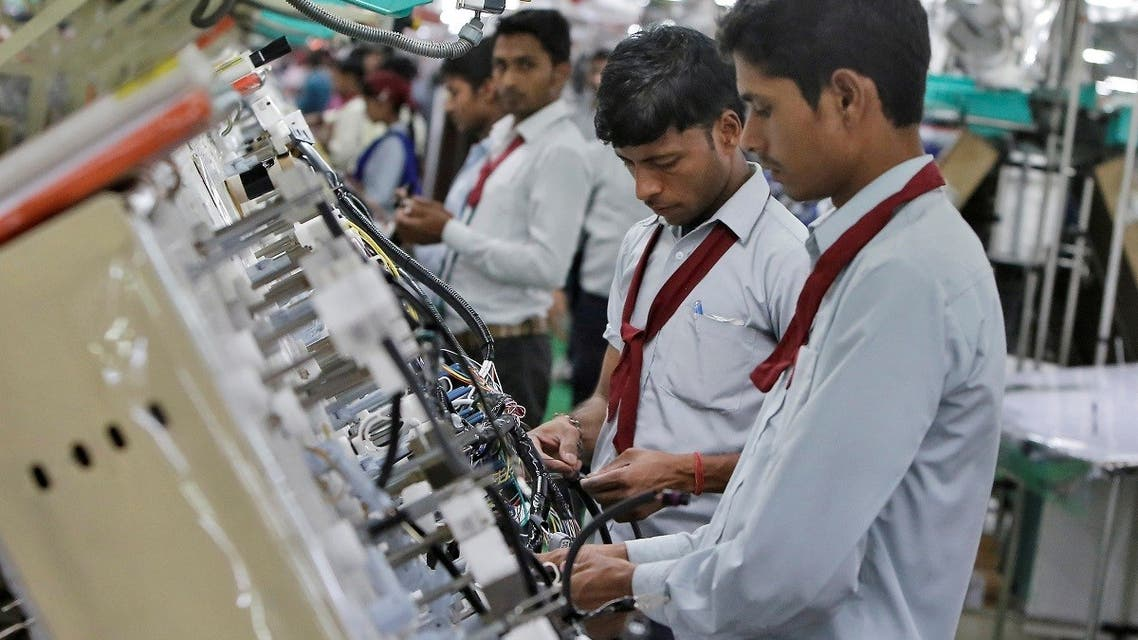 Employees of Motherson Sumi Systems Limited, work on a car wiring assembly line inside a factory in Noida on the outskirts of New Delhi, India. (File photo: Reuters)