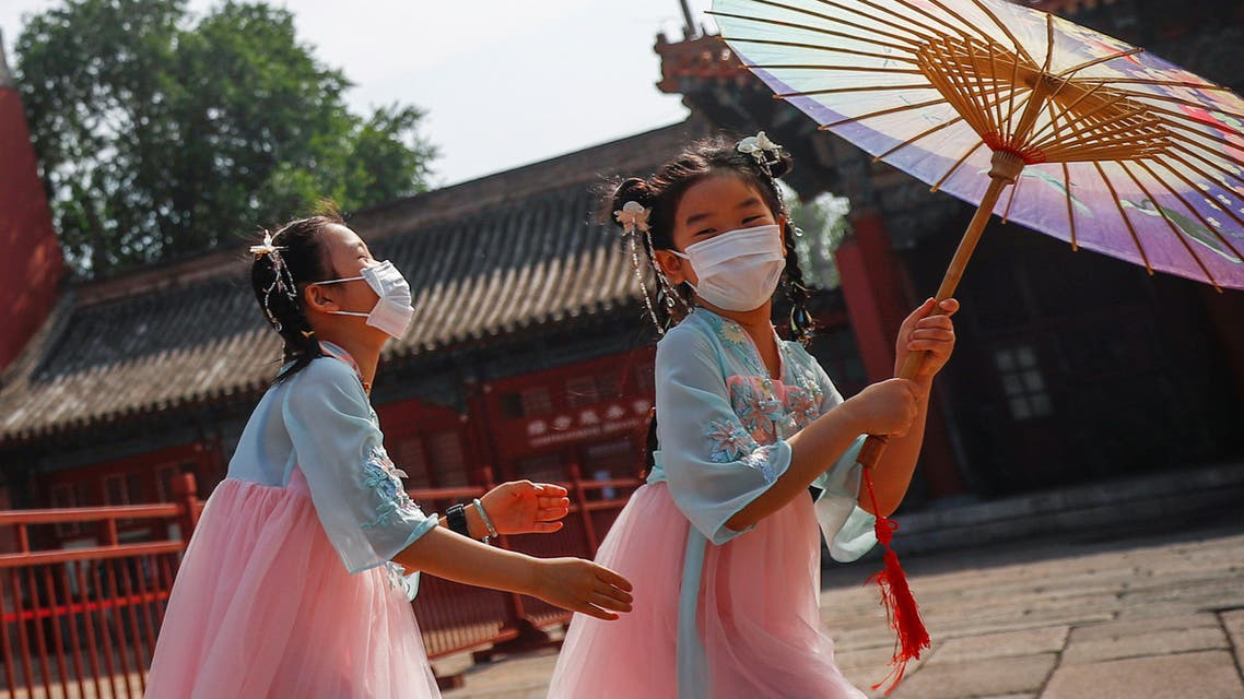 Children wearing protective face masks play near the entrance to the Forbidden City on the day of the opening of the National People's Congress (NPC) following the outbreak of the coronavirus disease (COVID-19), in Beijing, China May 22, 2020. REUTERS/Thomas Peter TPX IMAGES OF THE DAY
