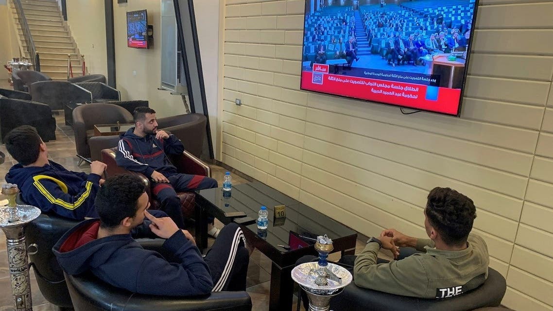 People watch Libya's parliament meet to vote on a unity government on a TV screen at a cafe in Misrata, Libya, on March 10, 2021. (Reuters)