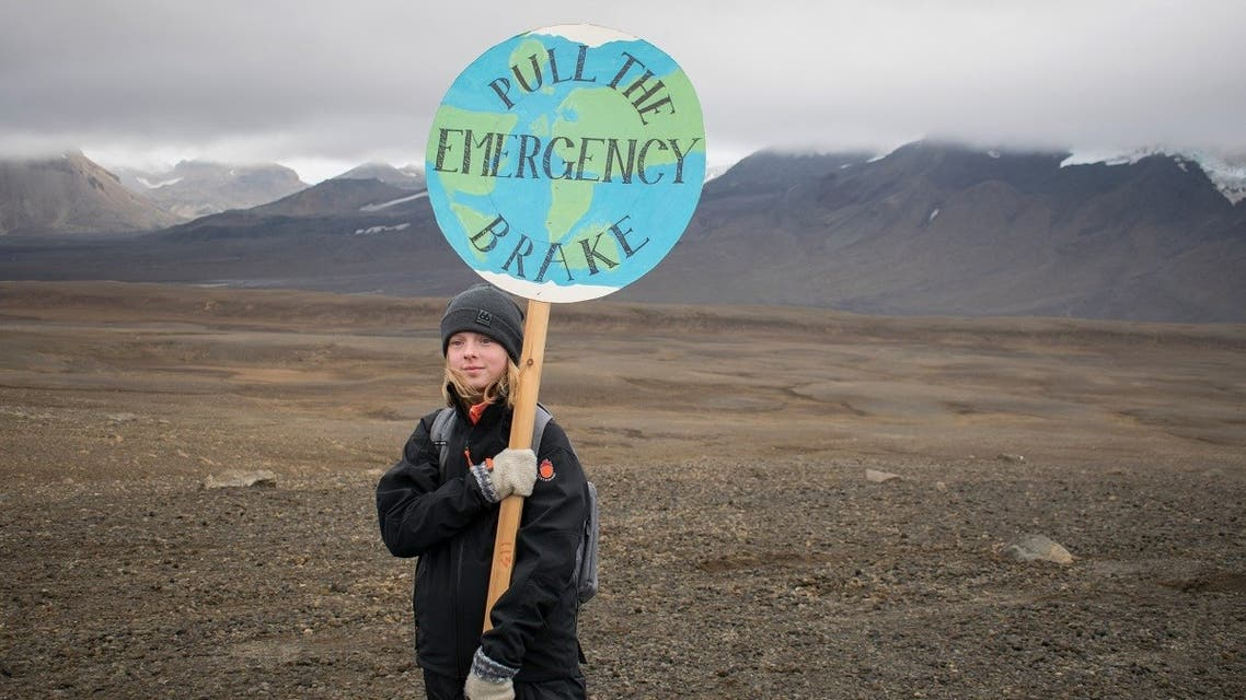 An Icelandic girl poses for a photo with a Pull the emergency brake sign near to where a monument was unveiled at the site of Okjokull, Iceland's first glacier lost to climate change in the west of Iceland on August 18, 2019. (AFP)