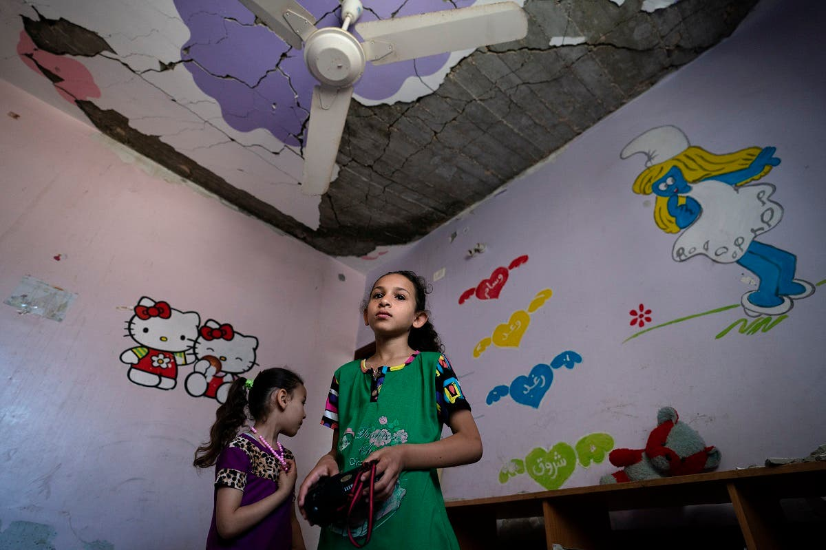 Shuroq Al-Masri, 9, and her sister Razan, 4, stand for a portrait in their bedroom that was severely damaged when an airstrike destroyed a neighboring building prior to a cease-fire that halted an 11-day war between Gaza's Hamas rulers and Israel, Wednesday, May 26, 2021, in Beit Hanoun, Gaza Strip. (AP)