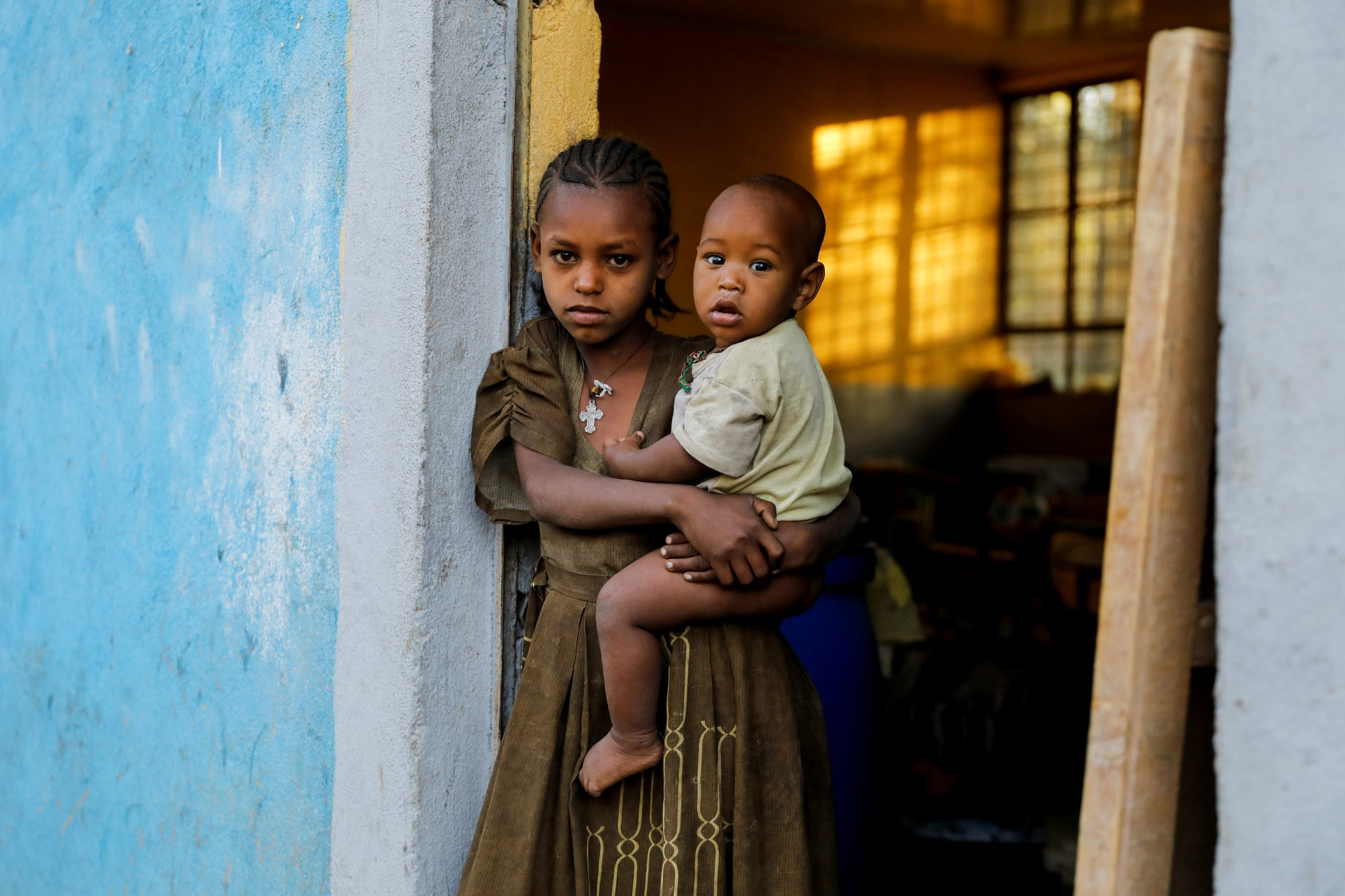 An 11-year-old girl holds her one-year-old brother Barakat at the doorway to a classroom now used as their living space, at the Tsehaye primary school, which was turned into a temporary shelter for people displaced by conflict, in the town of Shire, Tigray region, Ethiopia, March 15, 2021. (File Photo: Reuters)
