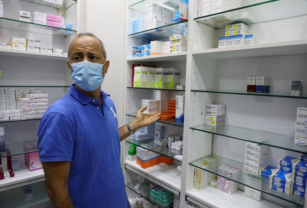 Mazen Bsat, a pharmacy owner, points at medication shelves during an interview with Reuters in Beirut, Lebanon May 28, 2021. (Reuters/Mohamed Azakir)