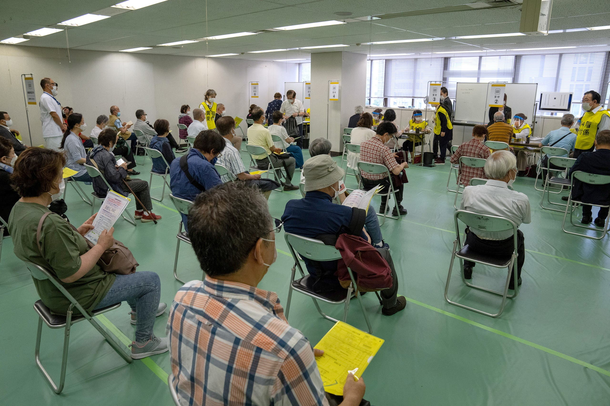 People wait to be processed after arriving to receive the Moderna coronavirus disease (COVID-19) vaccine at the newly-opened mass vaccination center in Tokyo, Japan, May 24, 2021. (Reuters)