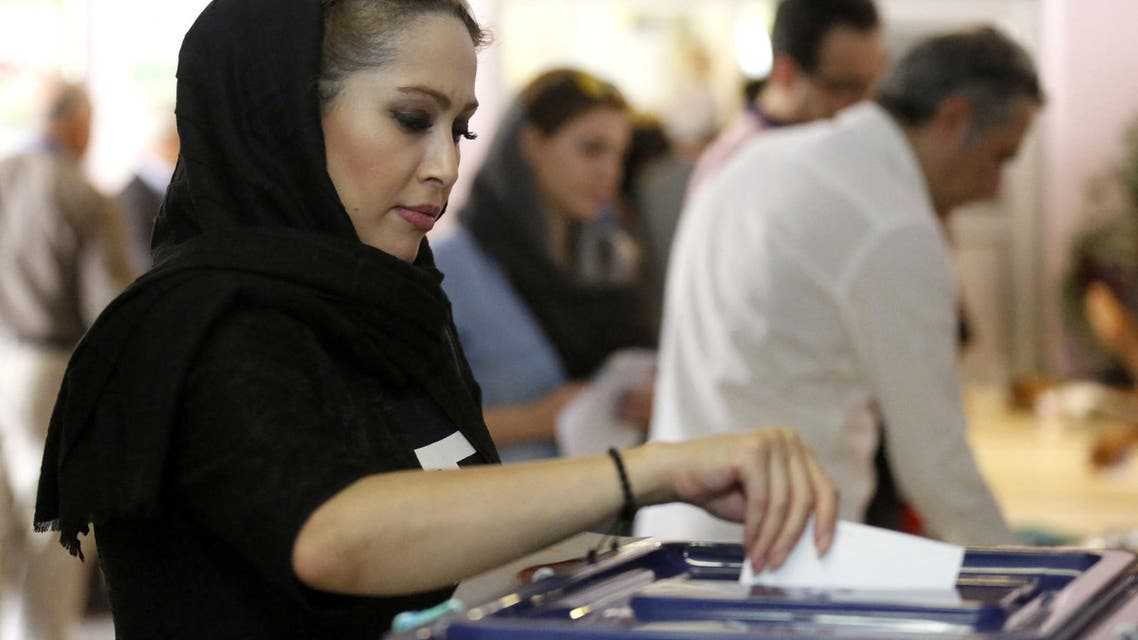 An Iranian woman casts her ballot for the presidential elections at a polling station in northern Tehran on May 19, 2017.