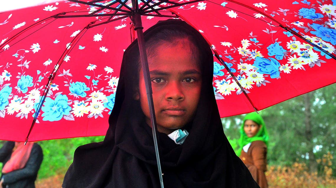 A Rohingya refugee holds an umbrella after she and a group arrived in Pulau Idaman, a small island off the coast of East Aceh in northern Sumatra on June 4, 2021. (File photo: AFP)