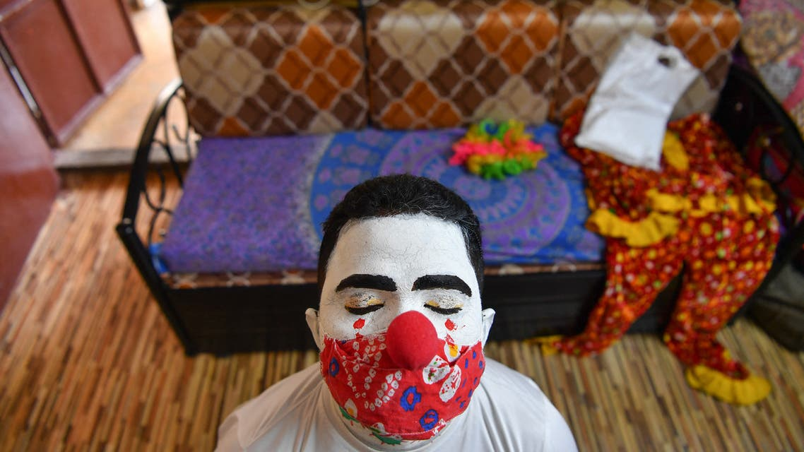 Social worker volunteer Ashok Kurmi, waits for his make-up to dry as he dresses like a clown before going into slums to start a sanitation work and spread awareness to follow the Covid-19 coronavirus safety protocols, at his home in Mumbai on June 2, 2021. (File photo: AFP)