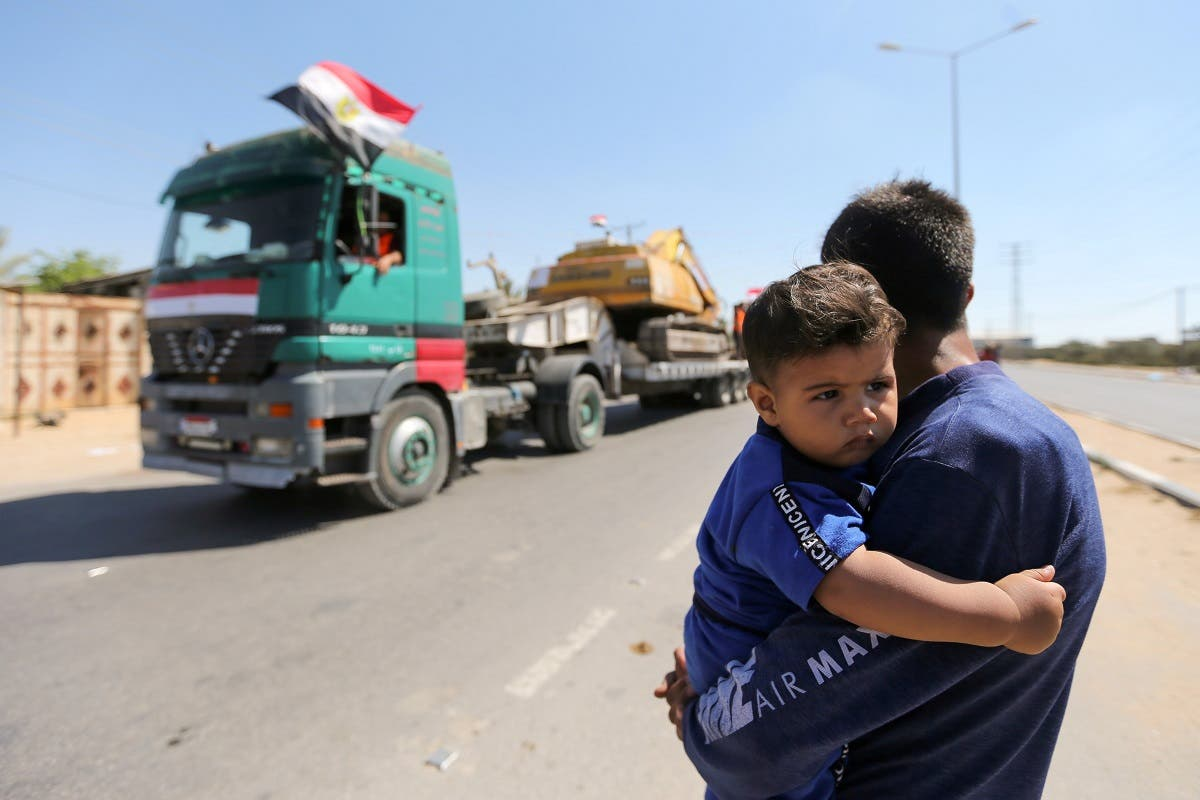 A man carrying a boy watches as building equipment, sent by Egypt for Palestinians, arrive in the southern Gaza Strip June 4, 2021. (Reuters)
