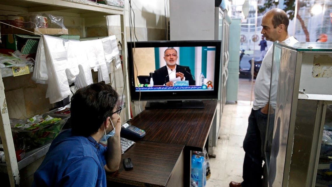 Iranians watch candidate Alireza Zakani speaking during the first televised debate between Iran presidential candidates, at a shop in Tehran on June 5, 2021. (AFP)