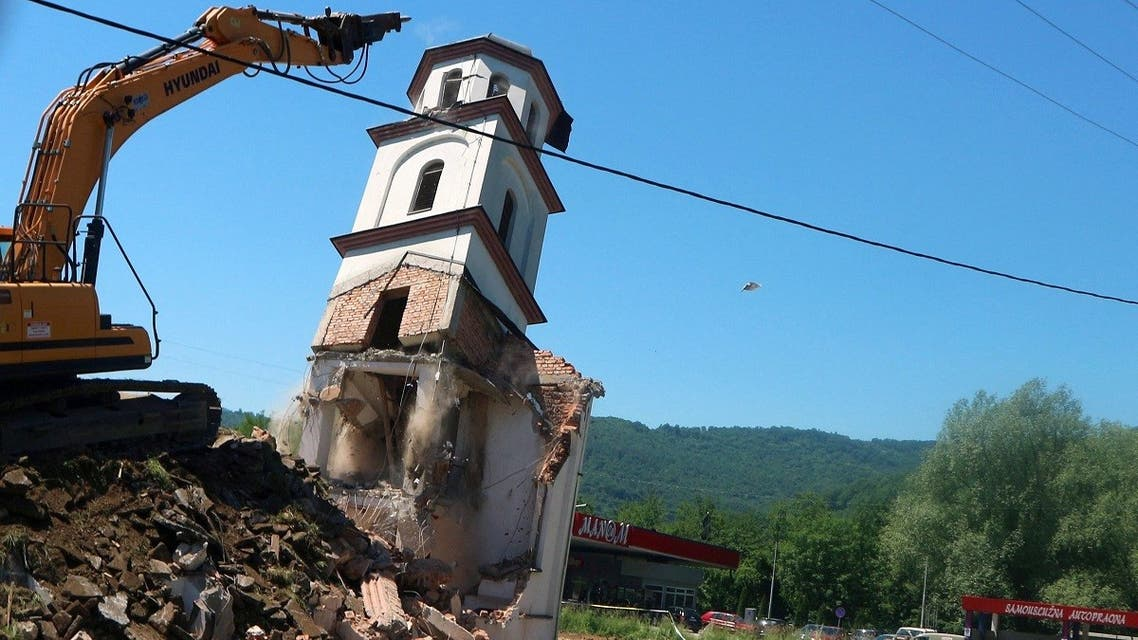 A digger demolishes an illegally constructed Serbian Orthodox church in Konjevic Polje, Eastern Bosnia on June 5, 2021, which was built in 1998 on land near Srebrenica, seized from Fata Orlovic, a Muslim refugee after the 1992-1995 civil war. (AFP)