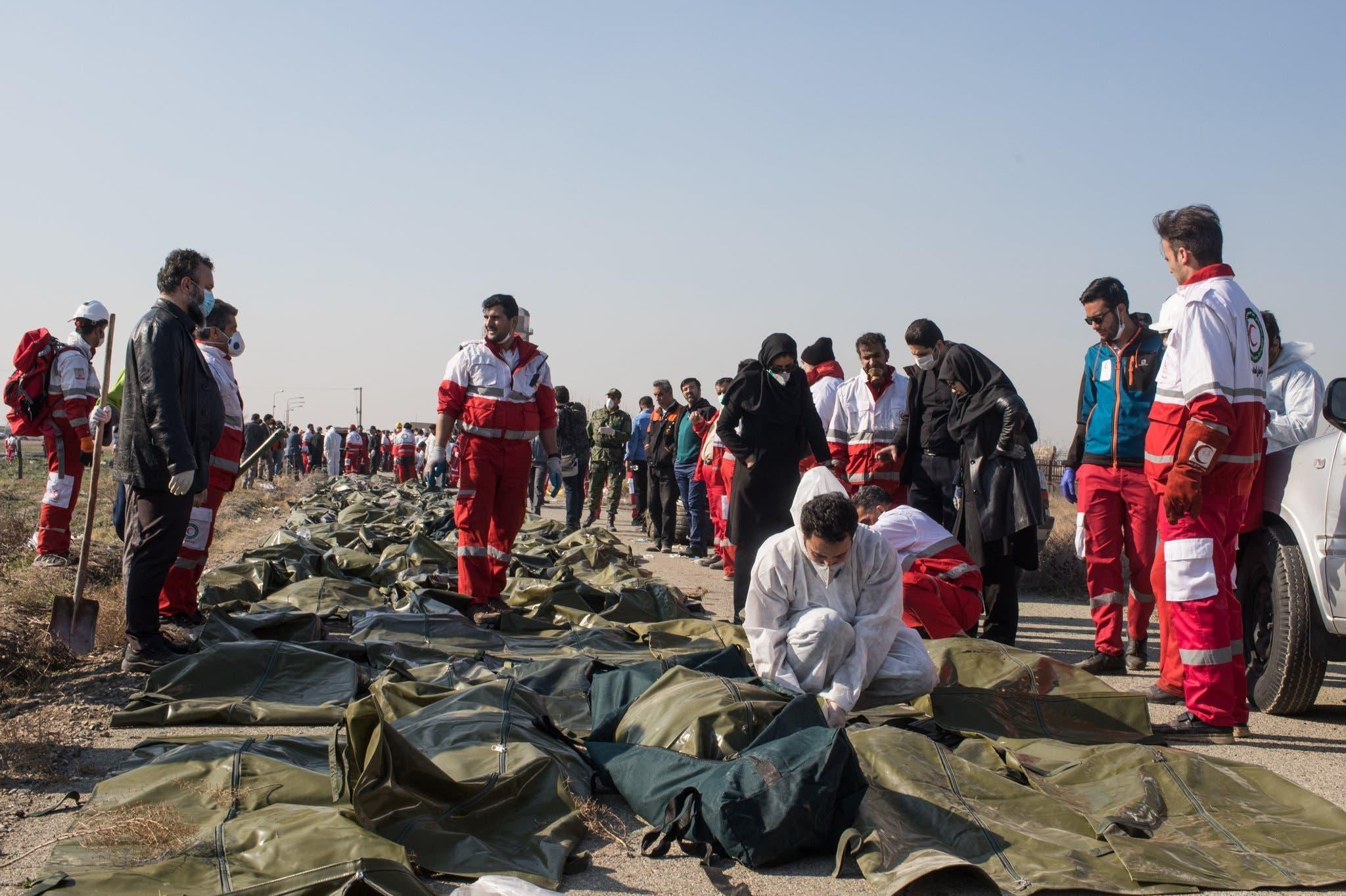 امدای کارکن نعشوں کو تدفین کے لیے تیار کر رہے ہیں
