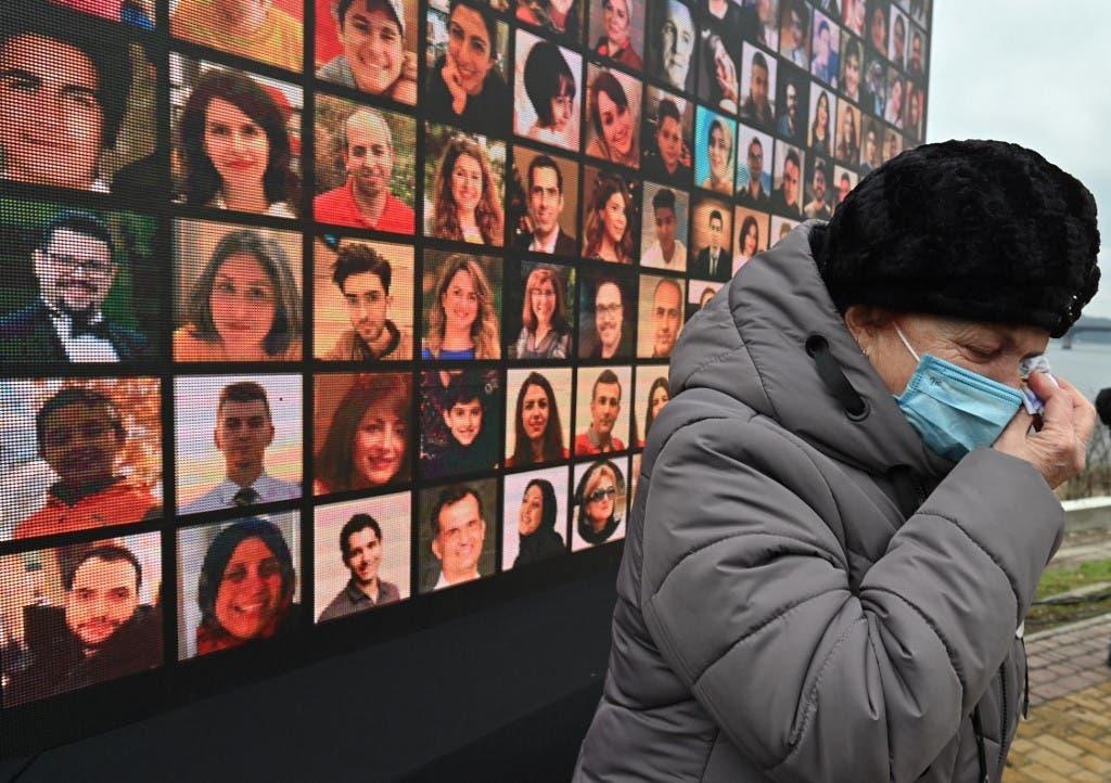 ایک نامعلوم خاتون حادثے میں ہلاک ہونے والوں کے تصاویر پر مبنی وال میورل کے سامنے